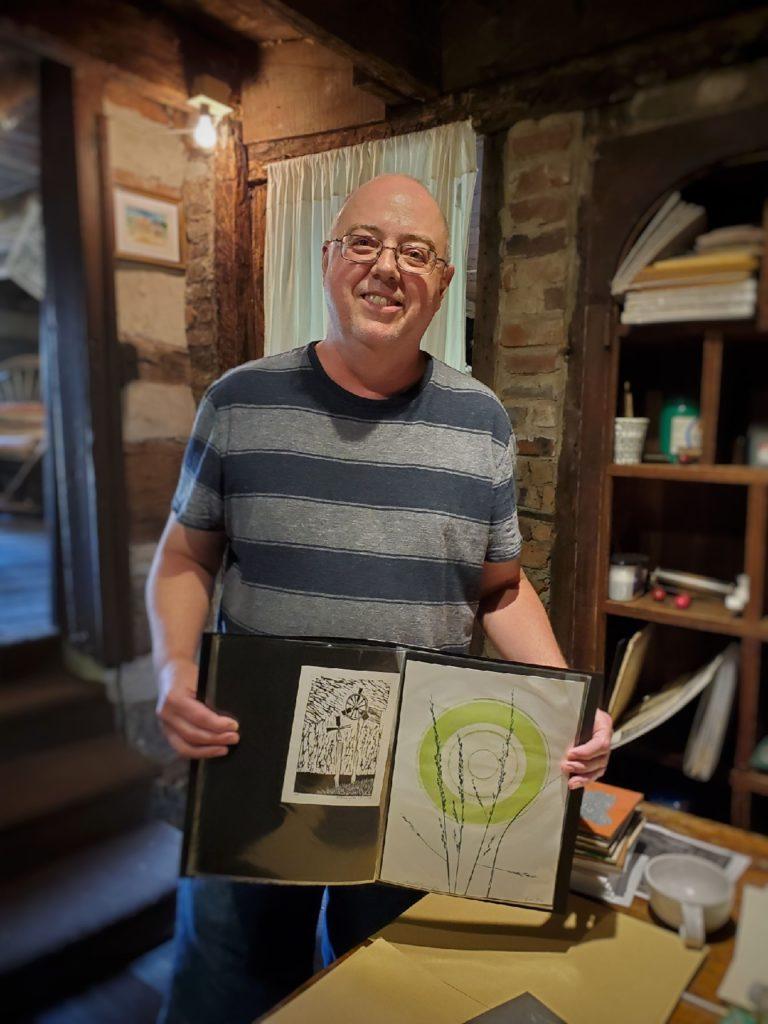 printmaker Arnold Pennington holding his portfolio
