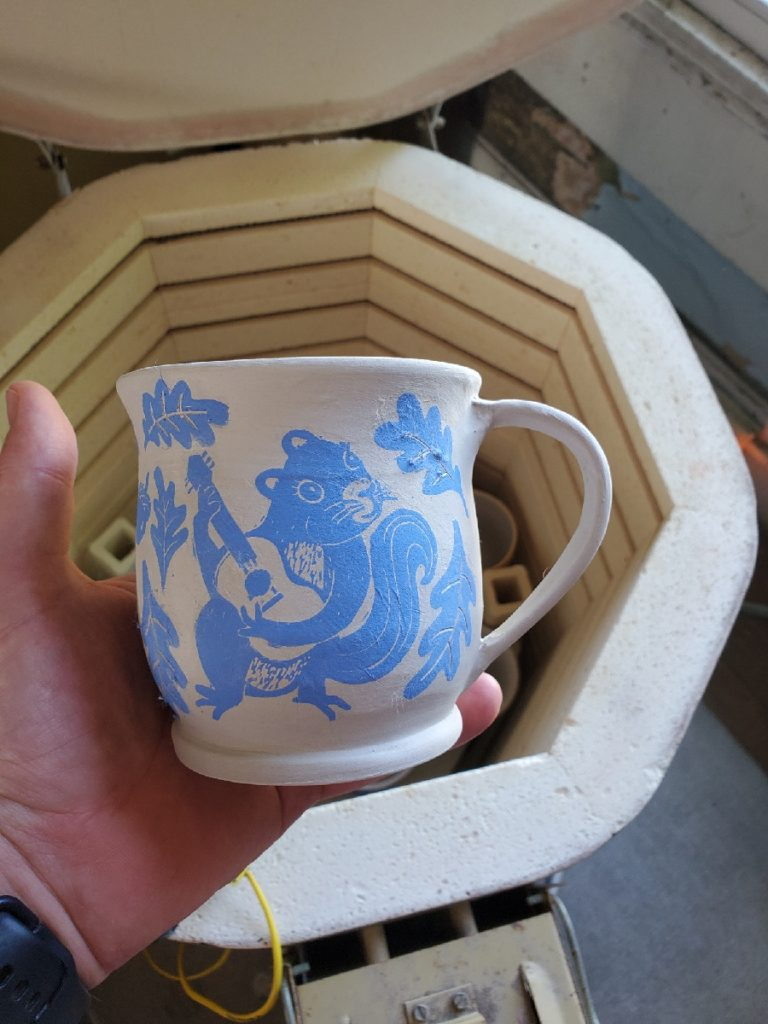 holding a greenware mug with decal of squirrel playing guitar