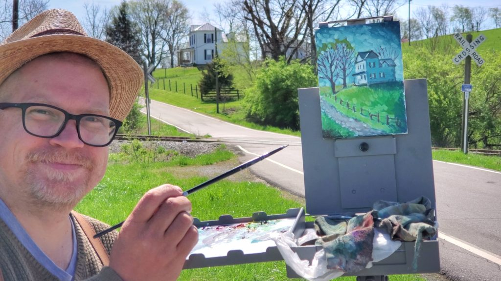 kentucky artist ken swinson painting at strodes run in mason county. the view is a house on a hill from a railroad track