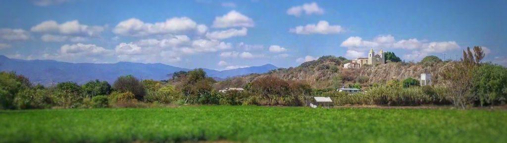 panoramic photo of green field and church pinetas in reyes etla