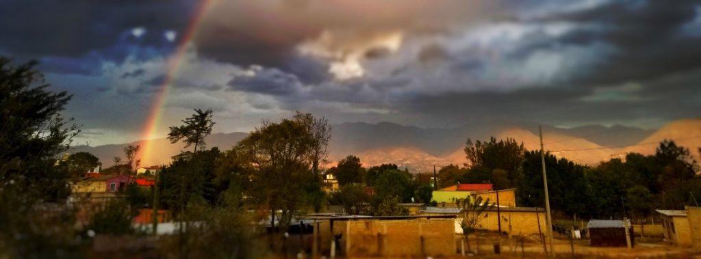 a dramatic sky with a rainbow over soledad etla, oaxaca mexico