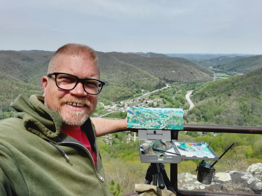artist standing with plein air painting from view on top of pine mountain