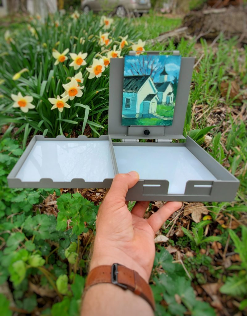 handheld strada micro easel with painting mounted and flowers in the background