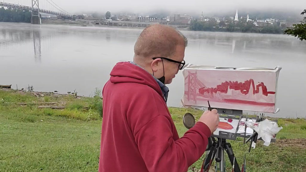photo of artist painting landscape from the ohio river