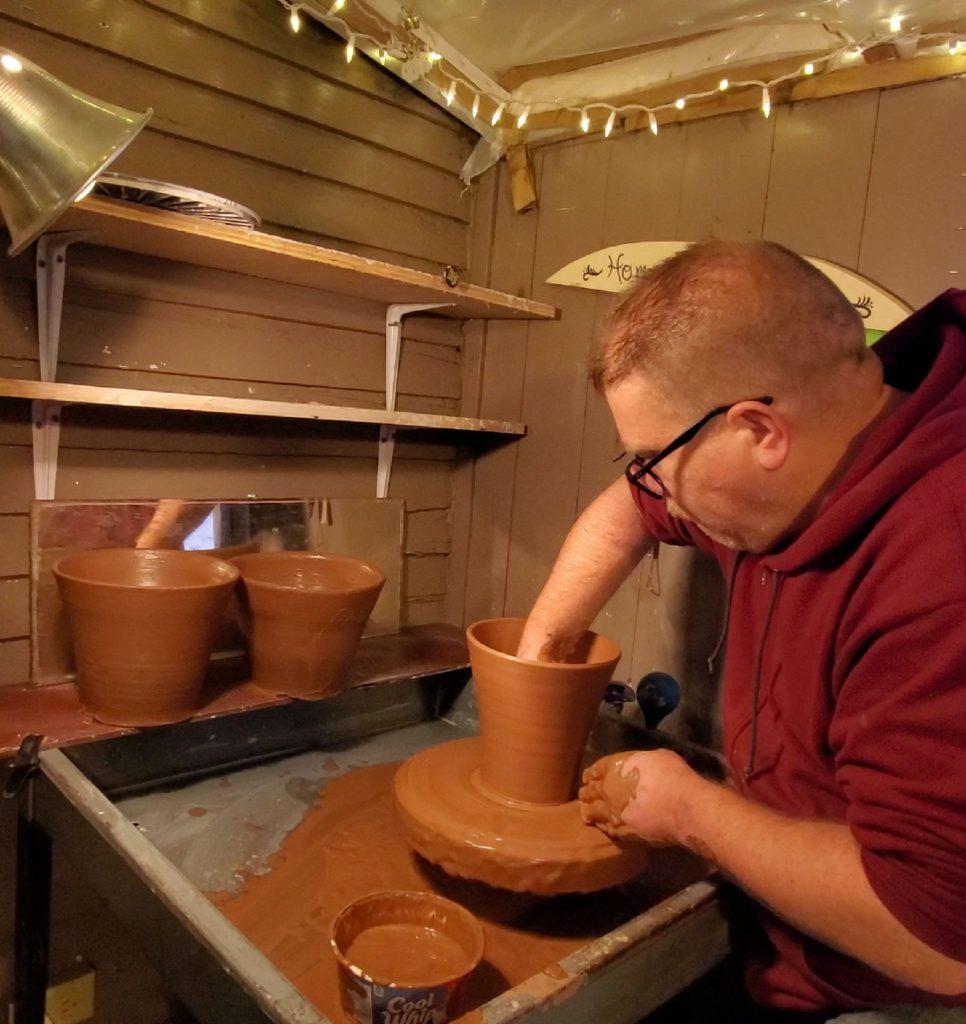 potter throwing clay flowerpots on wheel