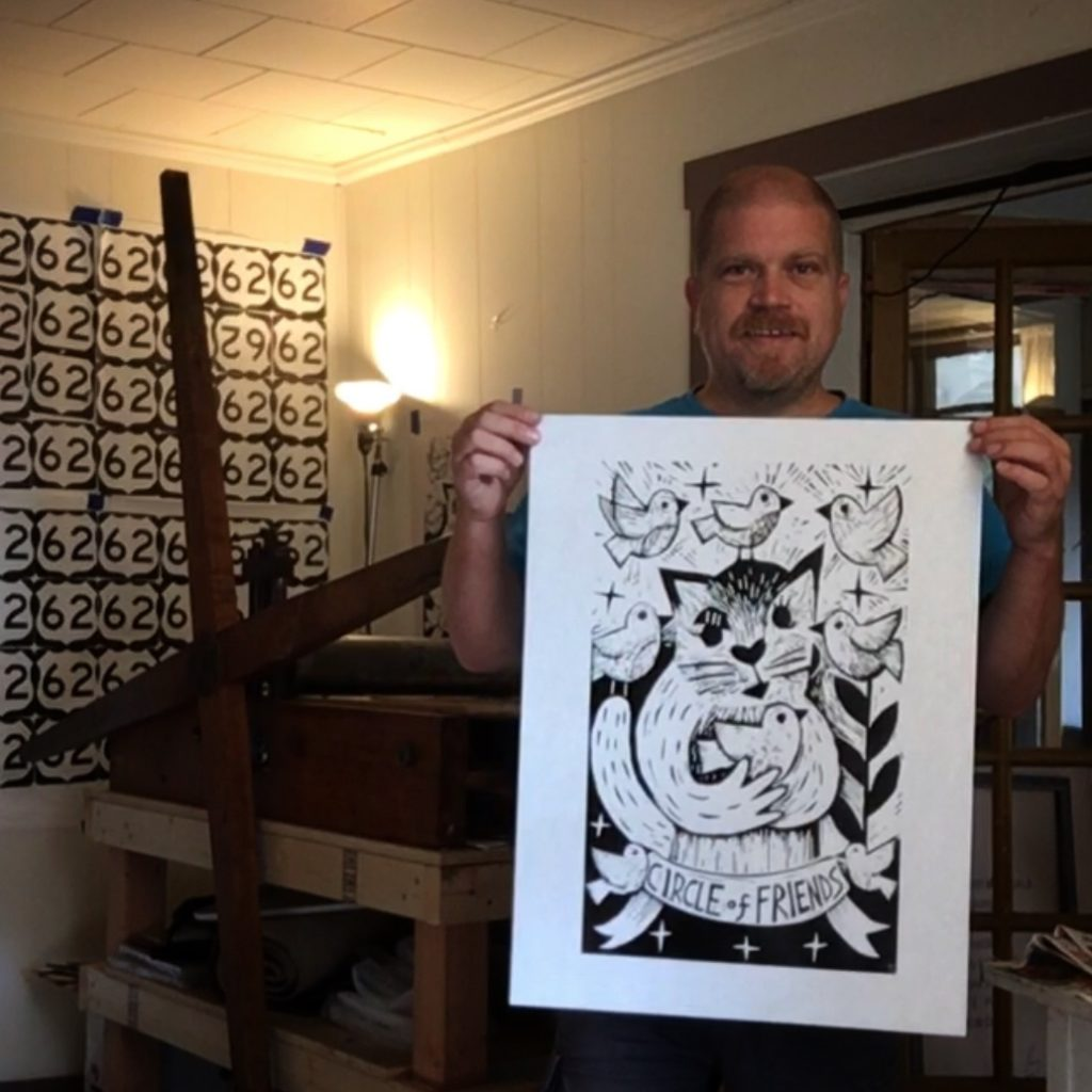 artist ken swinson holding a new woodcut of a cat holding a bird