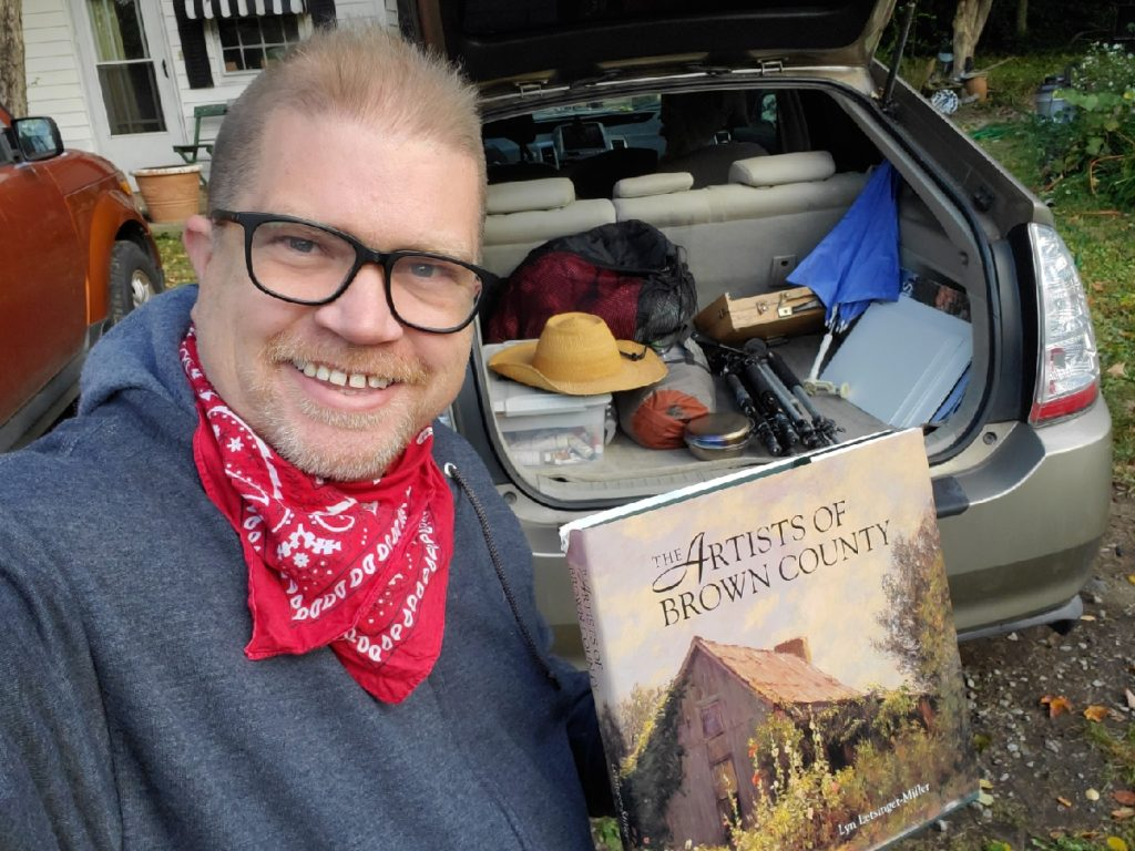 Artist with car packed with art supplies, holding a book of brown county artists