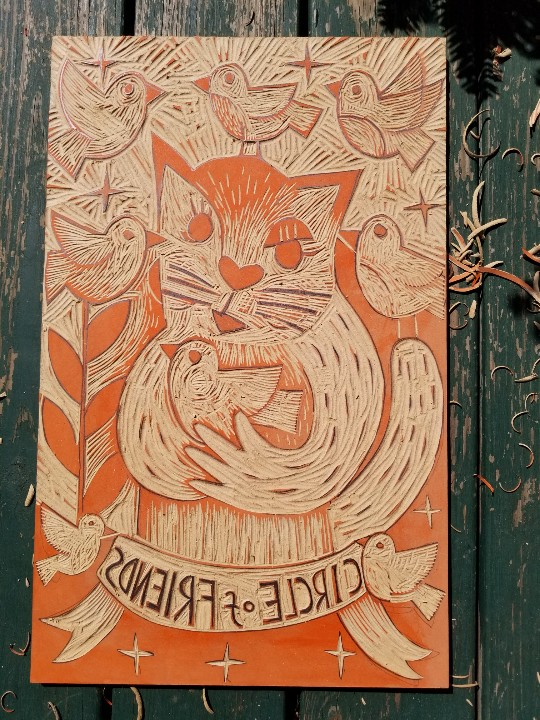 work in progress woodcut of a cat holding a bird ready to print
