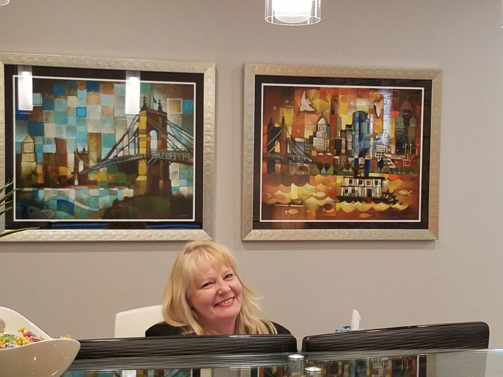 artist ken swinson paintings of  cincinnati framed and on display at reception desk