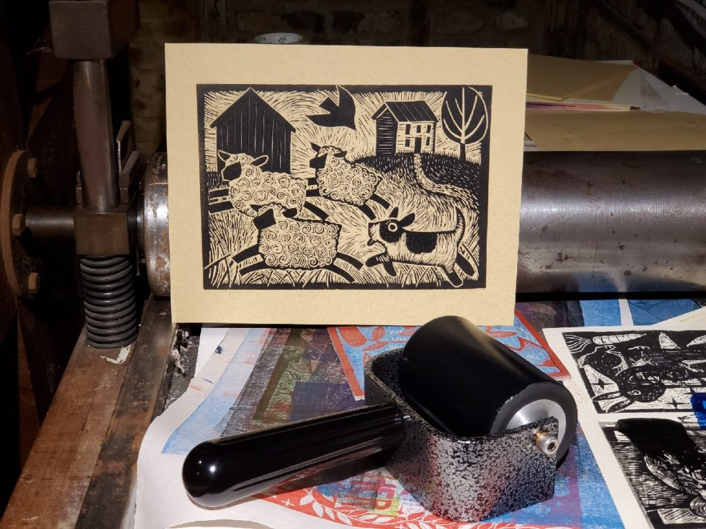 linocut of herding dog with sheep on a traditional press