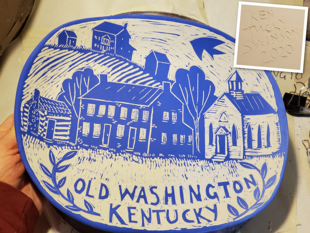 porcelain plate with sgraffito design of Old Washington, Kentucky. Log Cabin, Federal Brick buildind and white church house.