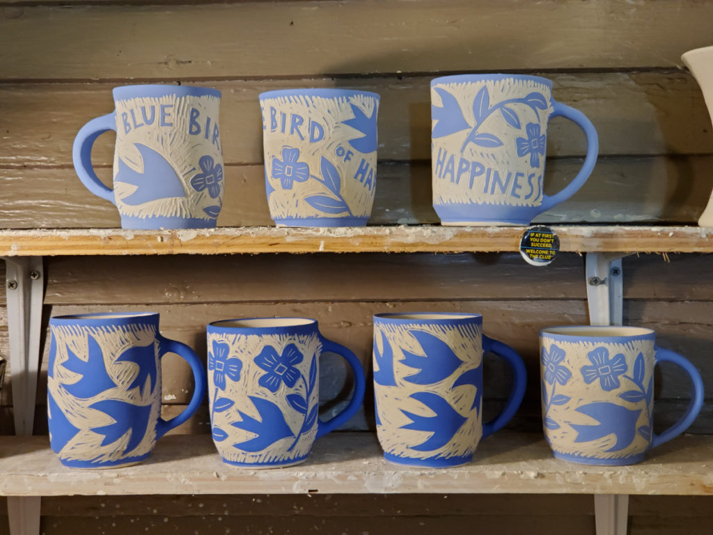 greenware porcelain cups with blue slip and sgraffito design of bluebirds and flowers